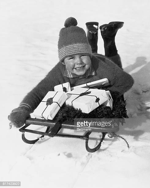 Young boy lays on a sled laden with Christmas presents and evergreen wreath. Undated photograph circa 1950.