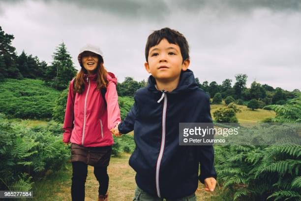 Young boy leading his mother through a field