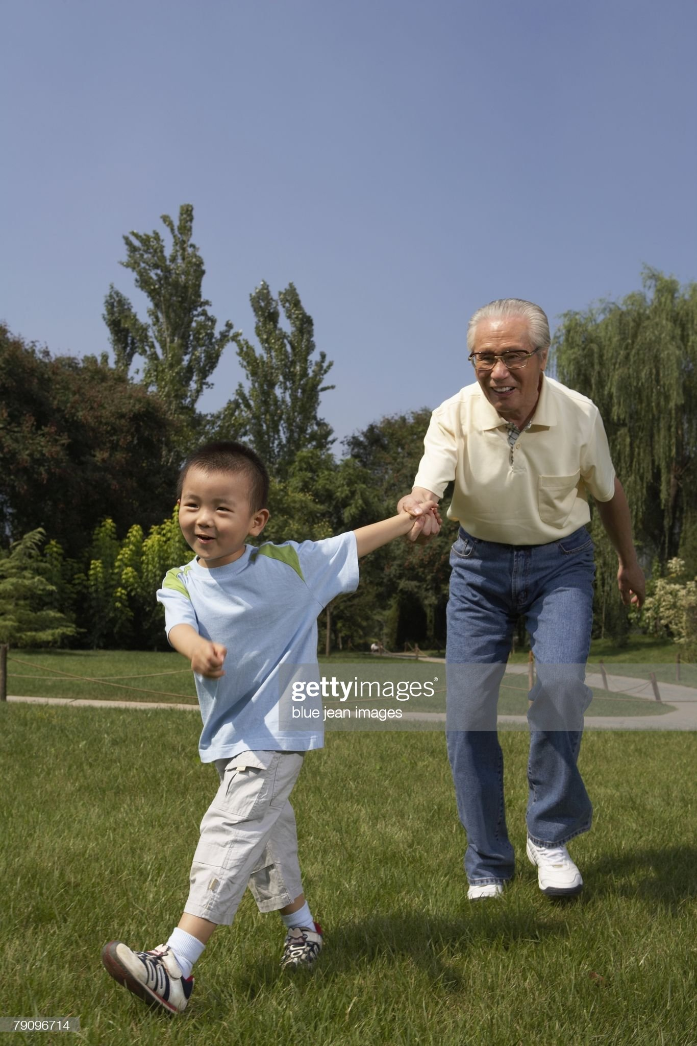 A young boy leads as his grandfather by the hand. : Stock Photo