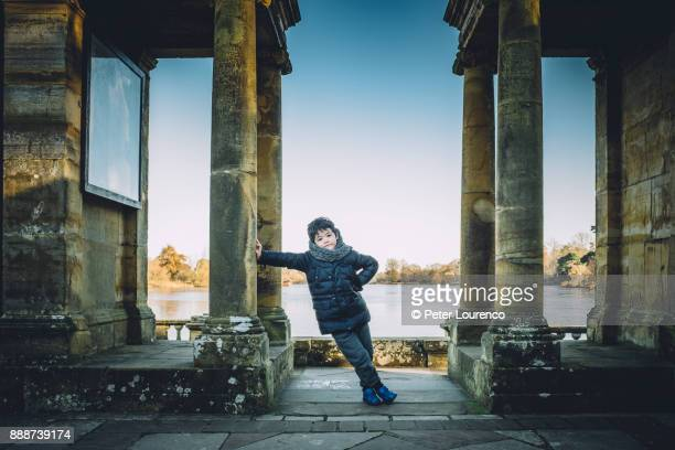 young boy leaning against a pillar. - peter lourenco imagens e fotografias de stock
