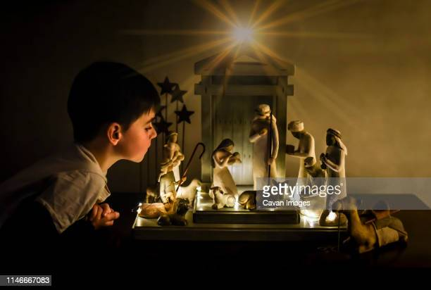 young boy leaning in looking closely at a ceramic nativity scene. - nativity scene stock pictures, royalty-free photos & images