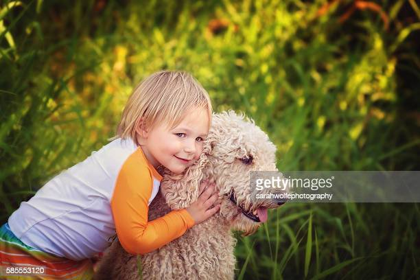 Young boy leaning in to hug  a standard poodle