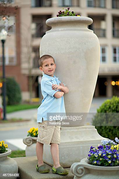 young boy leaning on a statue - khaki stock pictures, royalty-free photos & images