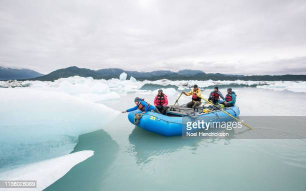 Young boy leaning out of raft to touch iceberg