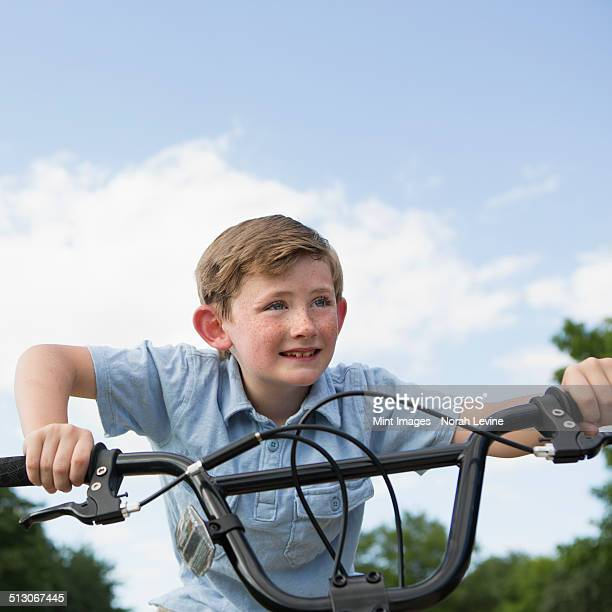 a young boy leaning over the handlebars of a bicycle. - handlebar stock photos and pictures