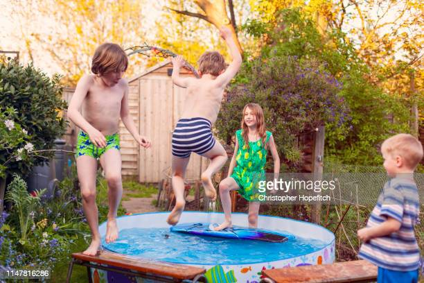 young boy leaping into a paddling pool - british people stock pictures, royalty-free photos & images
