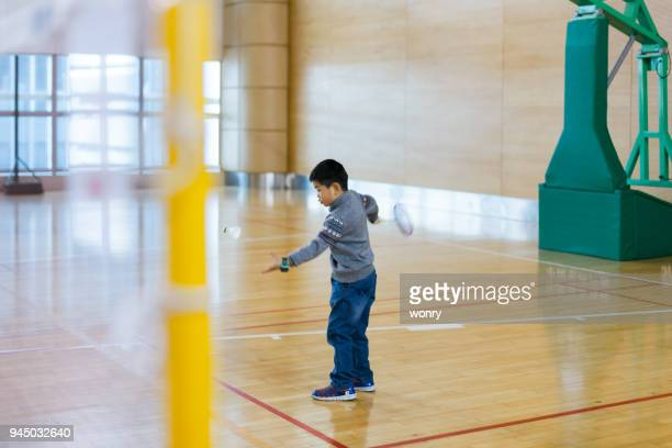 Young boy learning badminton indoors