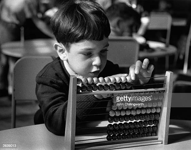 Young boy learning how to use an abacus at the Lycee, a French primary school in London. Original Publication: Picture Post - 8051 - A French School...