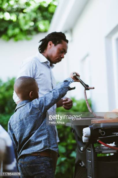 Young boy learning to barbecue with his dad side view