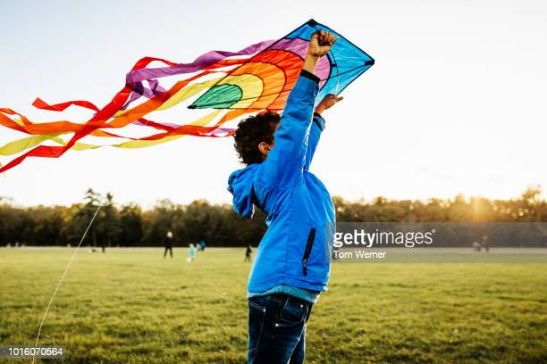 young boy learning to fly kite - black coat stock pictures, royalty-free photos & images
