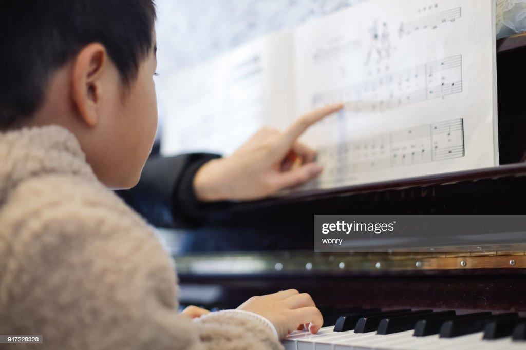 ピアノを弾くことを学ぶ若い男の子 : ストックフォト