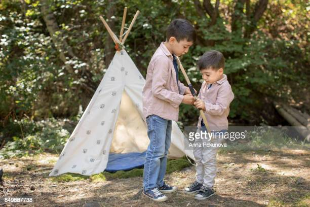 Young boy learning toddler brother to shoot with archery bow