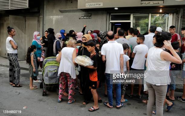 Young boy leaves a bakery with a bag of bread as people wait for their turn, in the neighbourhood of Nabaa in the Lebanese capital Beirut's southern...