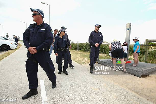 A young boy leaving the beach with his family watches on as police move into position to contain demonstrators opposing the Party for Freedom...
