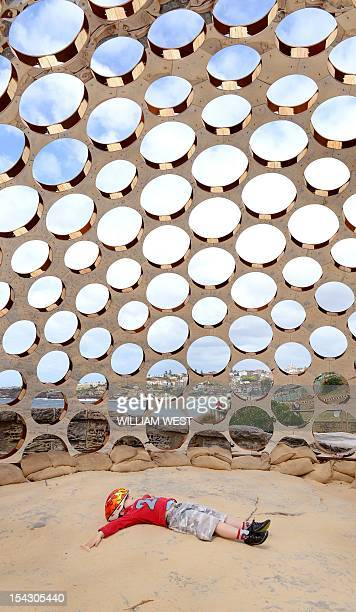 A young boy lies in the interior of a plywood timber and perspex dome titled 'Mirador' by artists Rachel Couper and Ivana Kuzmanovska at the...