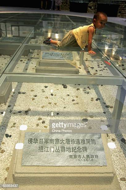 A young boy lies on a glass ground to see monuments built to commemorate the victims of Nanjing Massacre during an exhibition on the massacre at the...