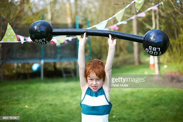Young boy lifting pretend barbell, outdoors