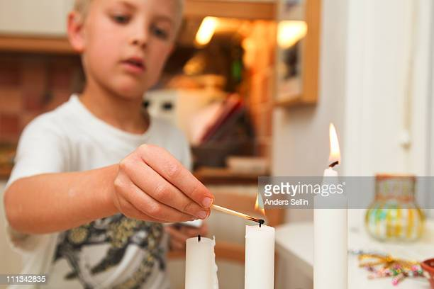 Young boy lightning candles