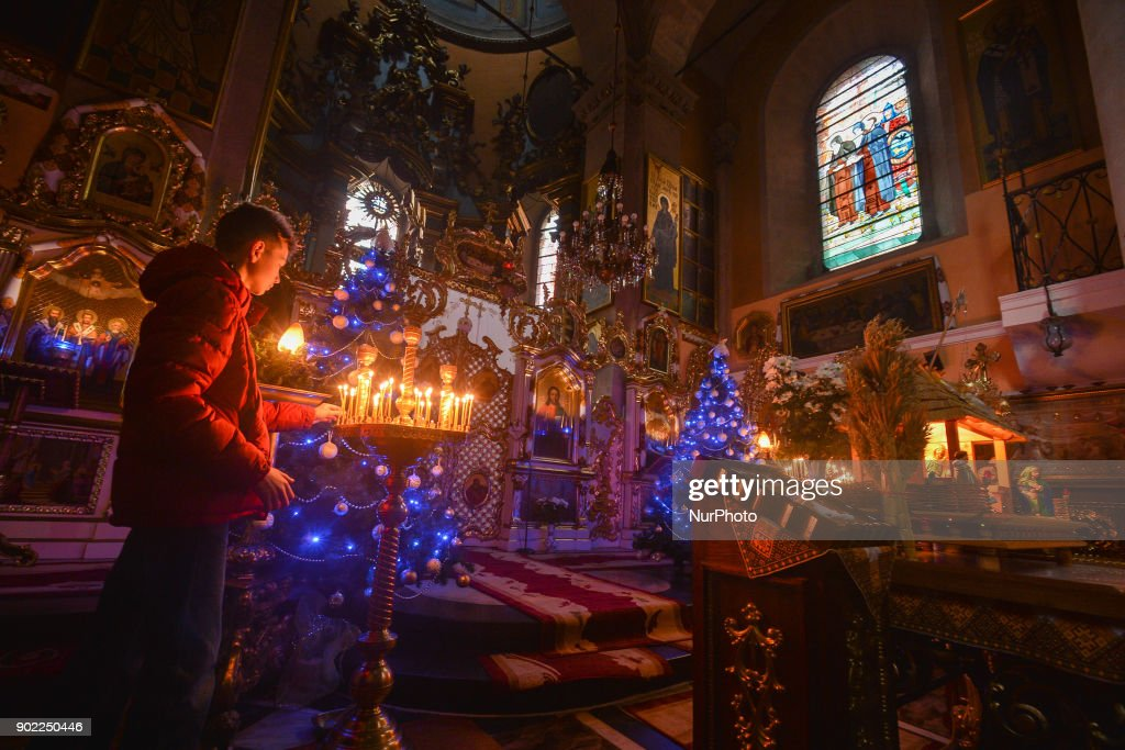 Eastern Orthodox Christmas.A Young Boy Lights A Candle On Eastern Orthodox Christmas