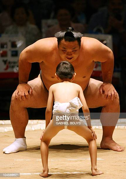 A young boy lines up face to face against a professional sumo wrestler during an exhibition before the start of the second day of the Grand Sumo...