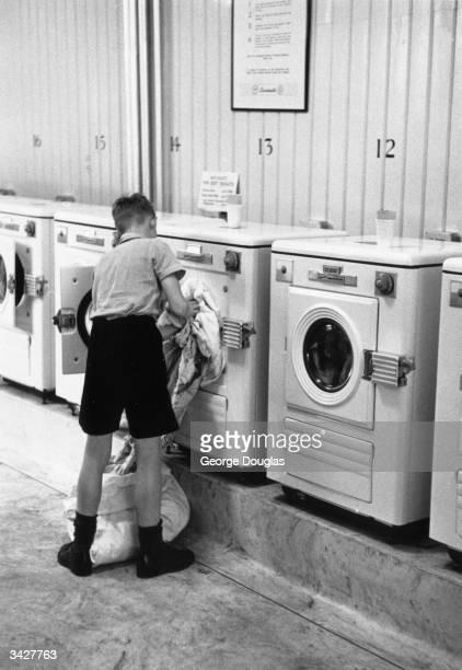 A young boy loading a Bendix washing machine at Britain's first selfservice laundrette in Bayswater London Original Publication Picture Post 6630...