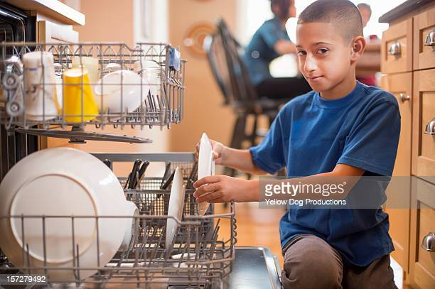 Young boy loading the dishwasher