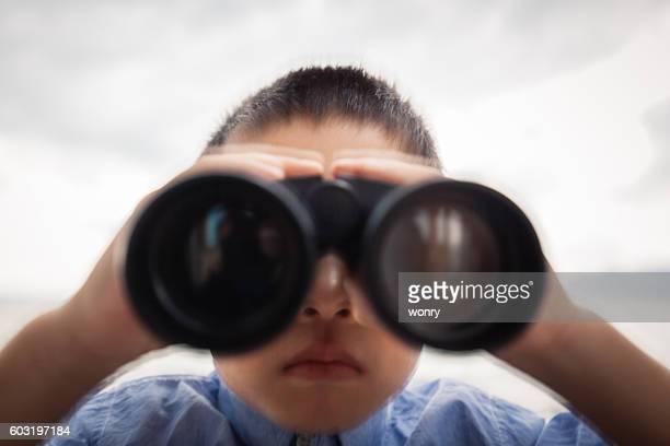 Young boy look through binoculars