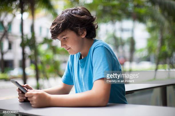 A young boy looking at a digital tablet, outdoors.