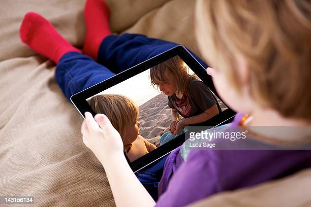young boy looking at a tablet - over the shoulder view stock pictures, royalty-free photos & images