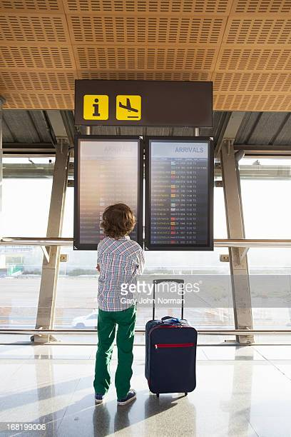 young boy looking at arrivals board at airport