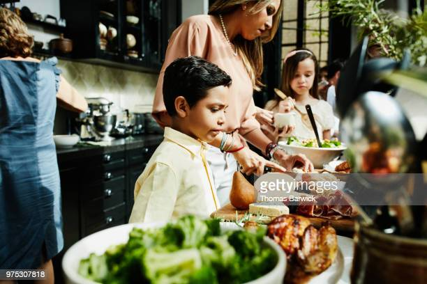 young boy looking at food in kitchen set out for family dinner party - differential focus stock pictures, royalty-free photos & images