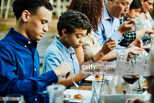 Young boy looking at food while dining with friends and family during outdoor dinner party