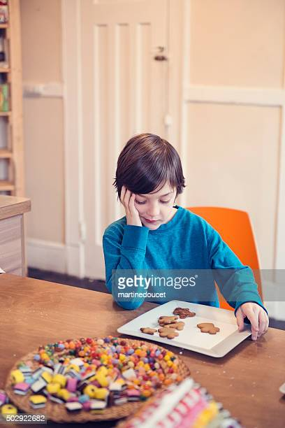 "young boy looking at gingerbread cookies with expressive face. - ""martine doucet"" or martinedoucet bildbanksfoton och bilder"