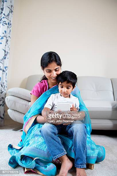 Young boy looking at phone with mum at home