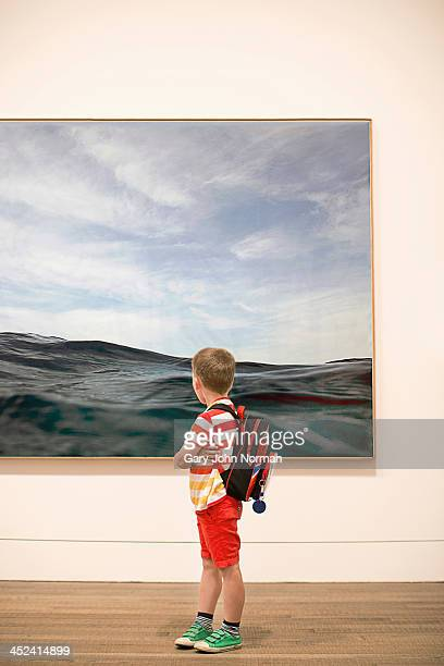 young boy looking at picture in gallery - museo fotografías e imágenes de stock
