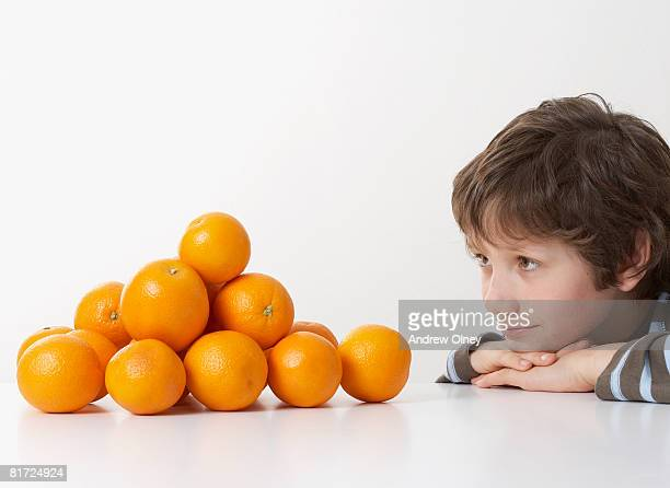 Young boy looking at pile of oranges
