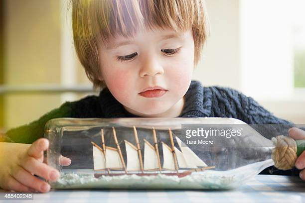 young boy looking at ship in a bottle