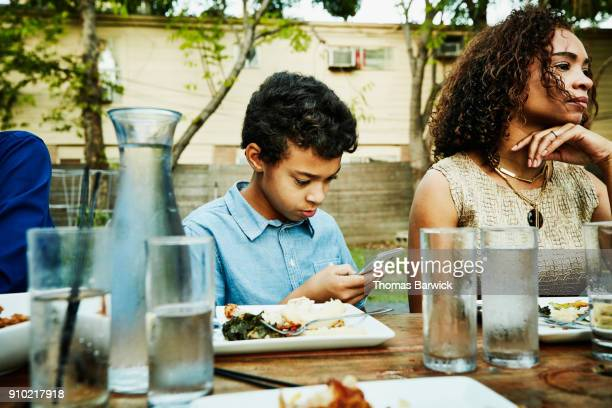 young boy looking at smartphone during outdoor family dinner - texas independence day stock pictures, royalty-free photos & images