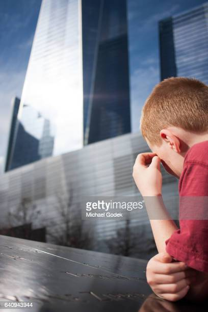 Young boy looking at the names engraved on the WTC Memorial trying to comprehend the magnitude of what he is seeing