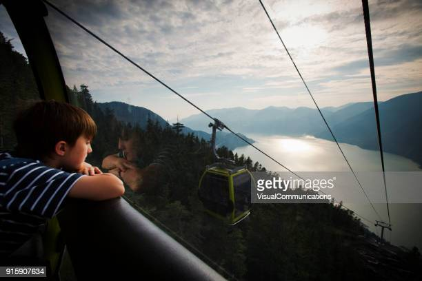 young boy looking at the view from gondola. - overhead cable car stock pictures, royalty-free photos & images
