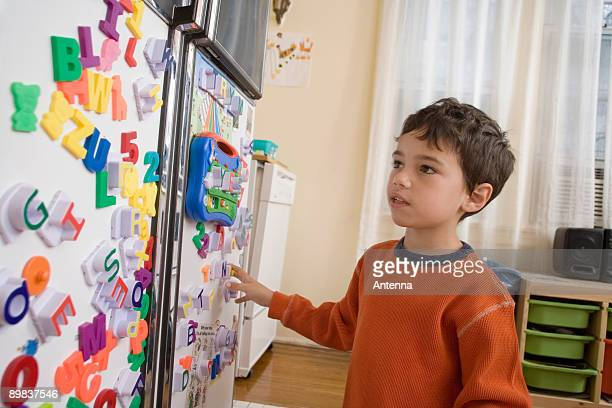 A young boy looking at toy magnets on a refrigerator door