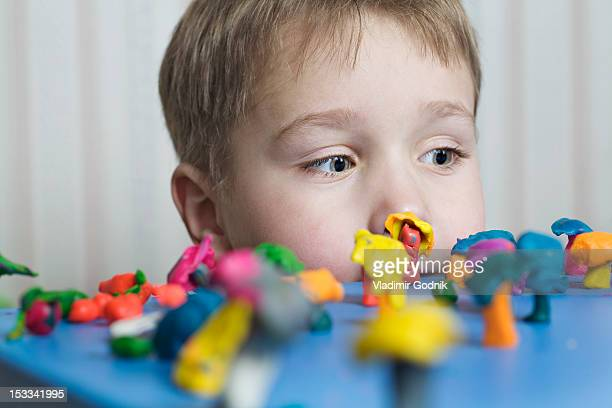 a young boy looking at various shapes made from child's play clay - clay stock pictures, royalty-free photos & images