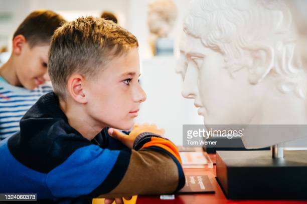 young boy looking closely at classical bust in museum - education stock pictures, royalty-free photos & images