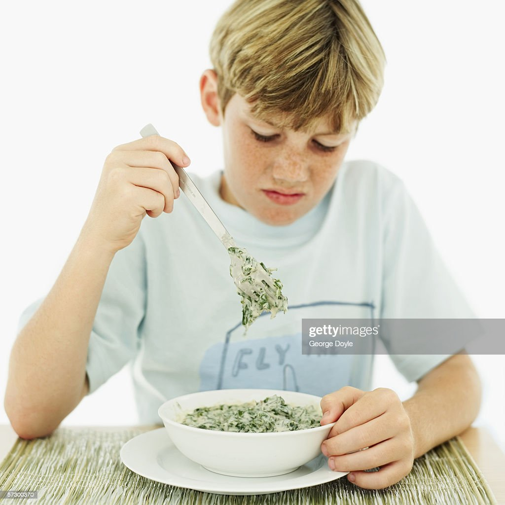 Young boy (12-13) looking down at a bowl of vegetable soup : Stock Photo