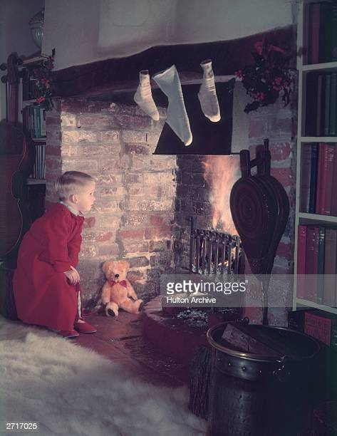 A young boy looking for Father Christmas up the chimney