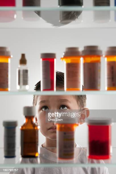 young boy looking into a medicine cabinet - medicine cabinet stock pictures, royalty-free photos & images
