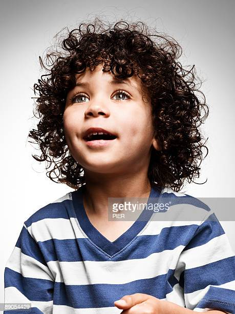 young boy looking into distance - curly stock pictures, royalty-free photos & images