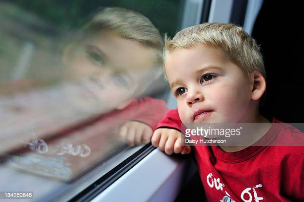 young boy looking out of a train window - ashford kent stock photos and pictures