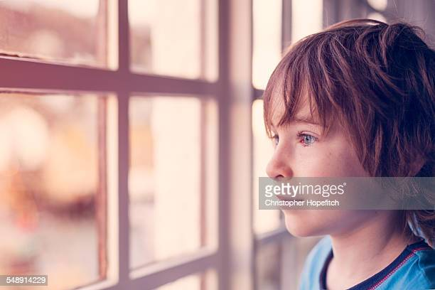 Young boy looking out of a window
