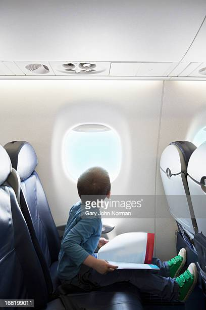 young boy looking out of aeroplane window